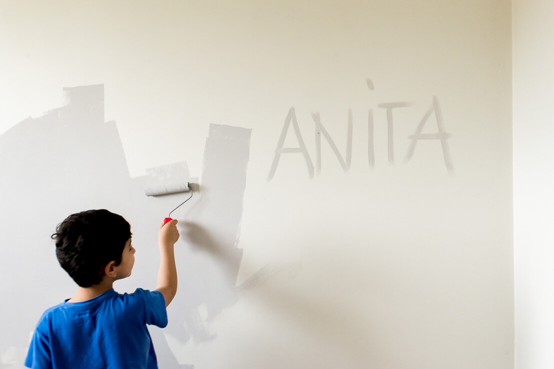 Boy painting the bedroom wall with the name of his little sister Anita during a pregnancy family photoshoot