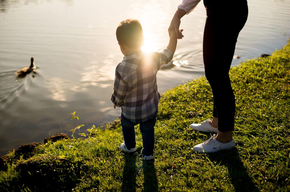 Mom and son, holding hands in front of a lake, sun reflecting in the lake