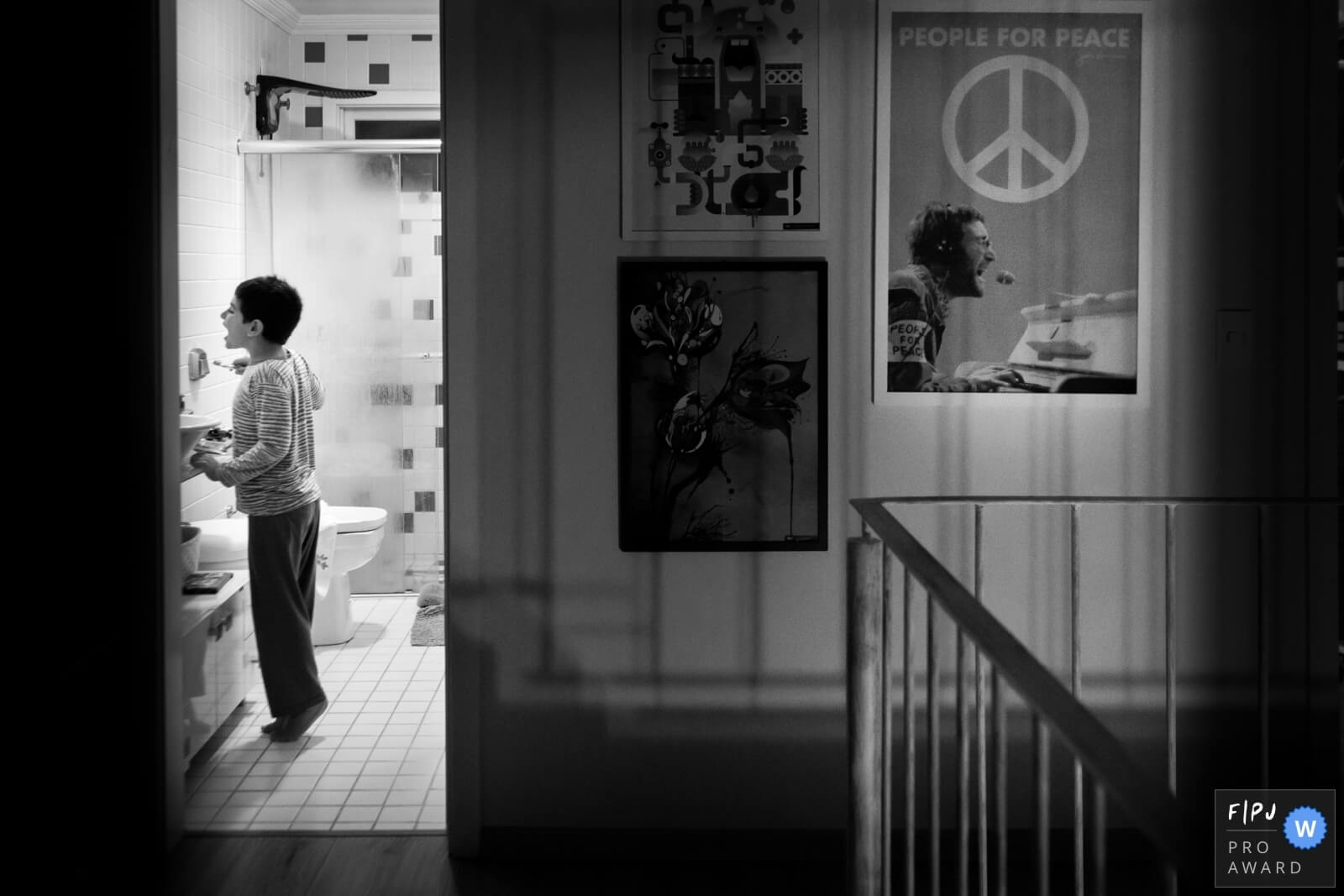 Black and white picture of a child in the bathroom brushing his teeth
