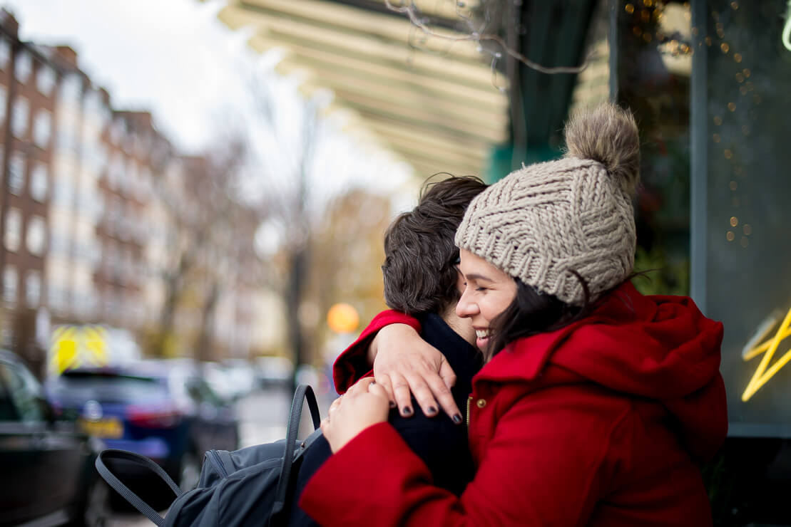 Couple hugging and smiling during winter maternity photoshoot in Notting Hill