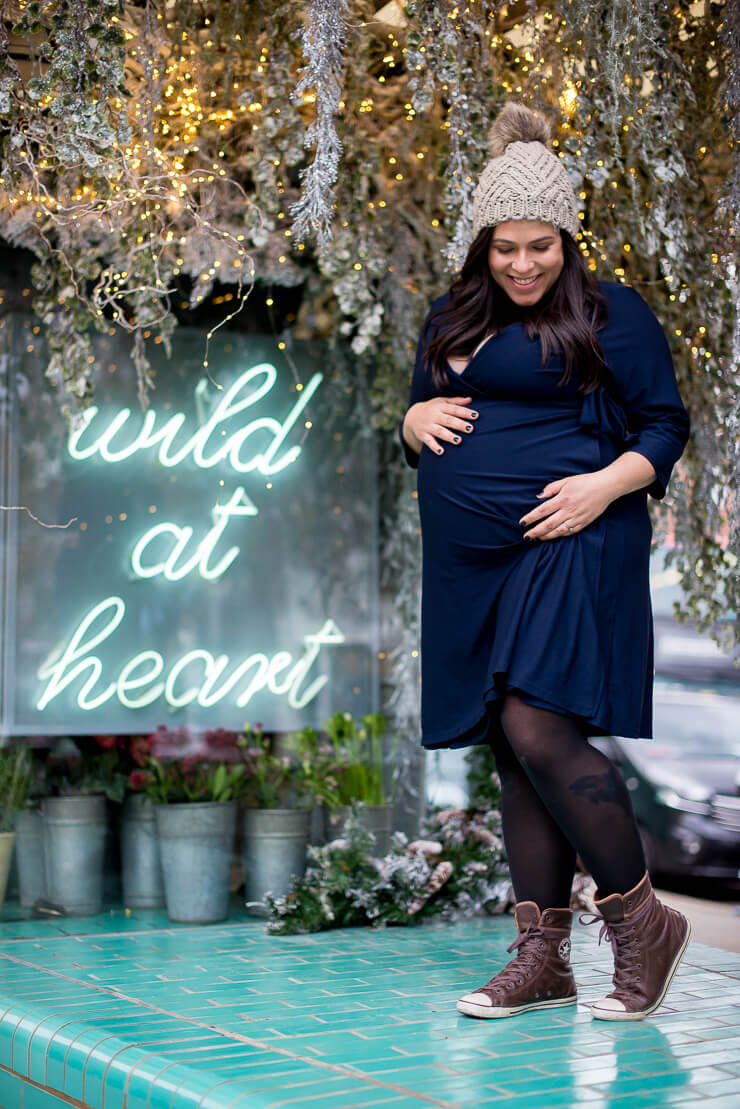 pregnant woman stroking her belly in front of a flowery plaque during winter maternity photoshoot in Notting Hill