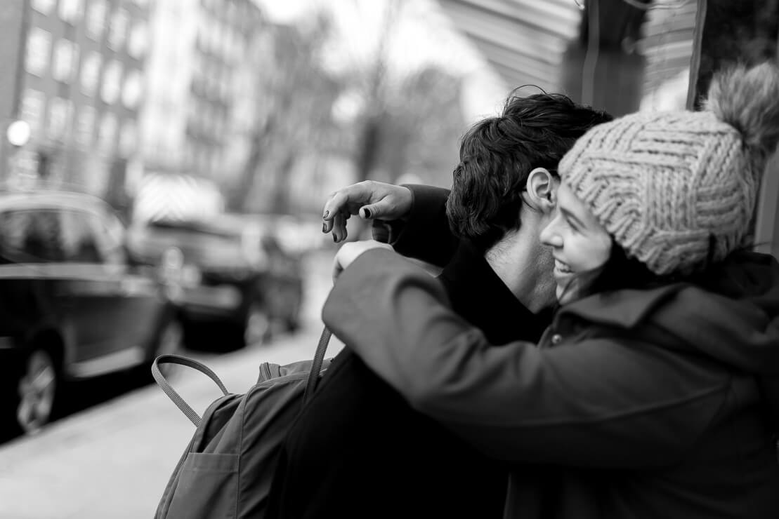 Black and white picture of couple hugging and smiling during winter maternity photoshoot in Notting Hill