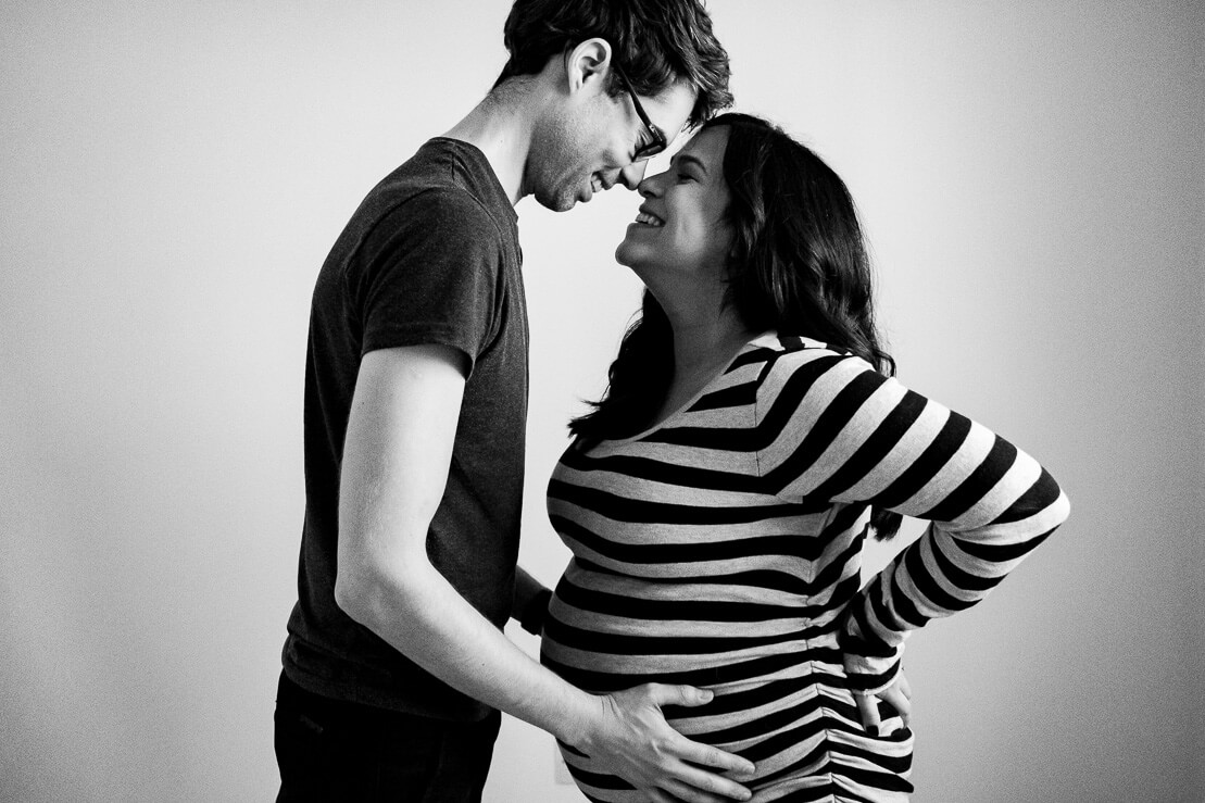 black and white photo of pregnant couple during winter maternity photoshoot in Notting Hill