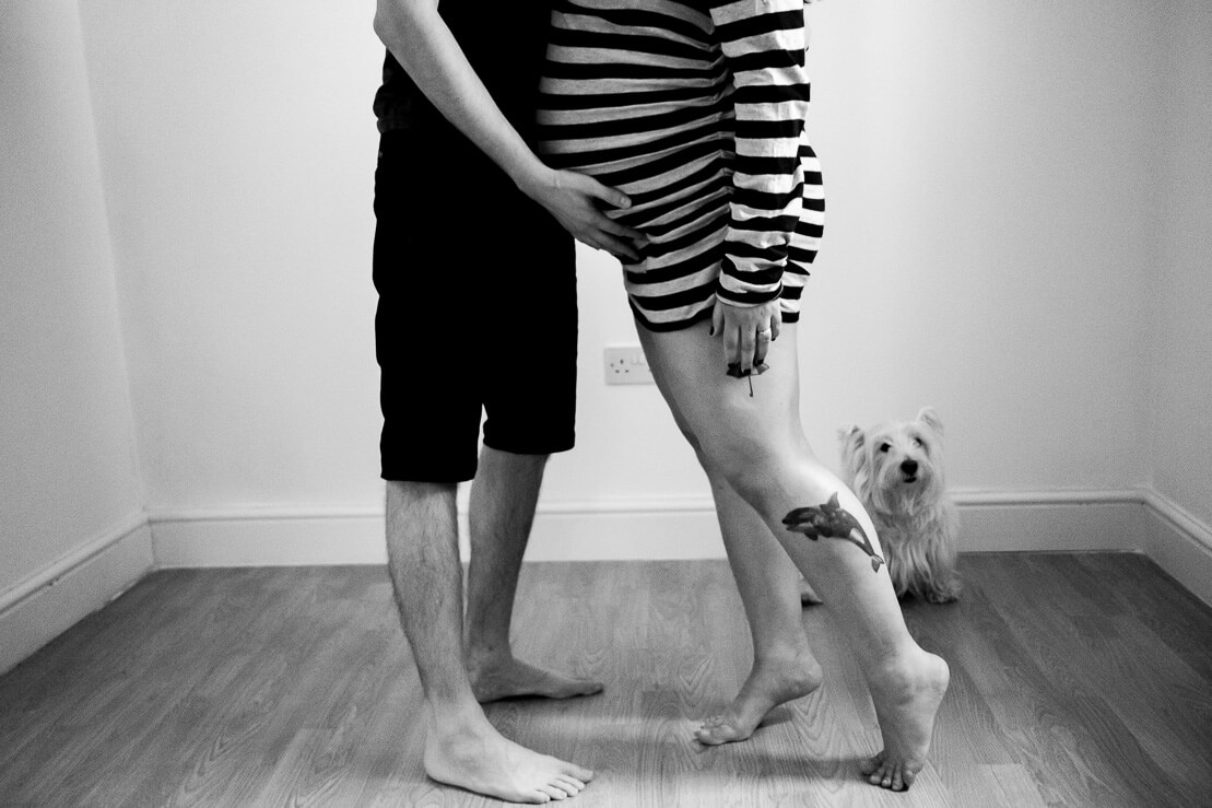 Black and white photo with the legs of a pregnant couple with a dog in the background during winter maternity photoshoot in Notting Hill