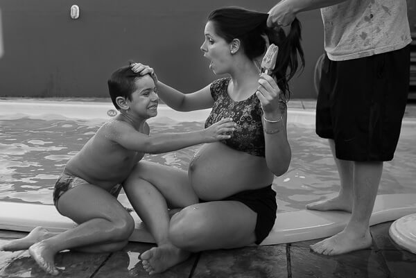 Lifestyle Maternity Photography: Child trying to take the ice cream from his pregnant mom during a