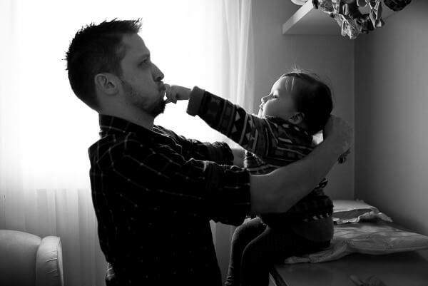 Documentary Family photography London: kid putting her finger inside dad's mouth