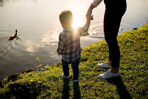 Lifestyle family photography London: mother and son in front of a lake holding hands, sun reflecting on them
