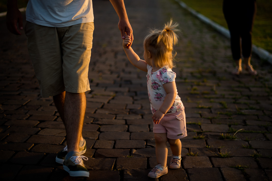 Kid holding dad's hand at sunset