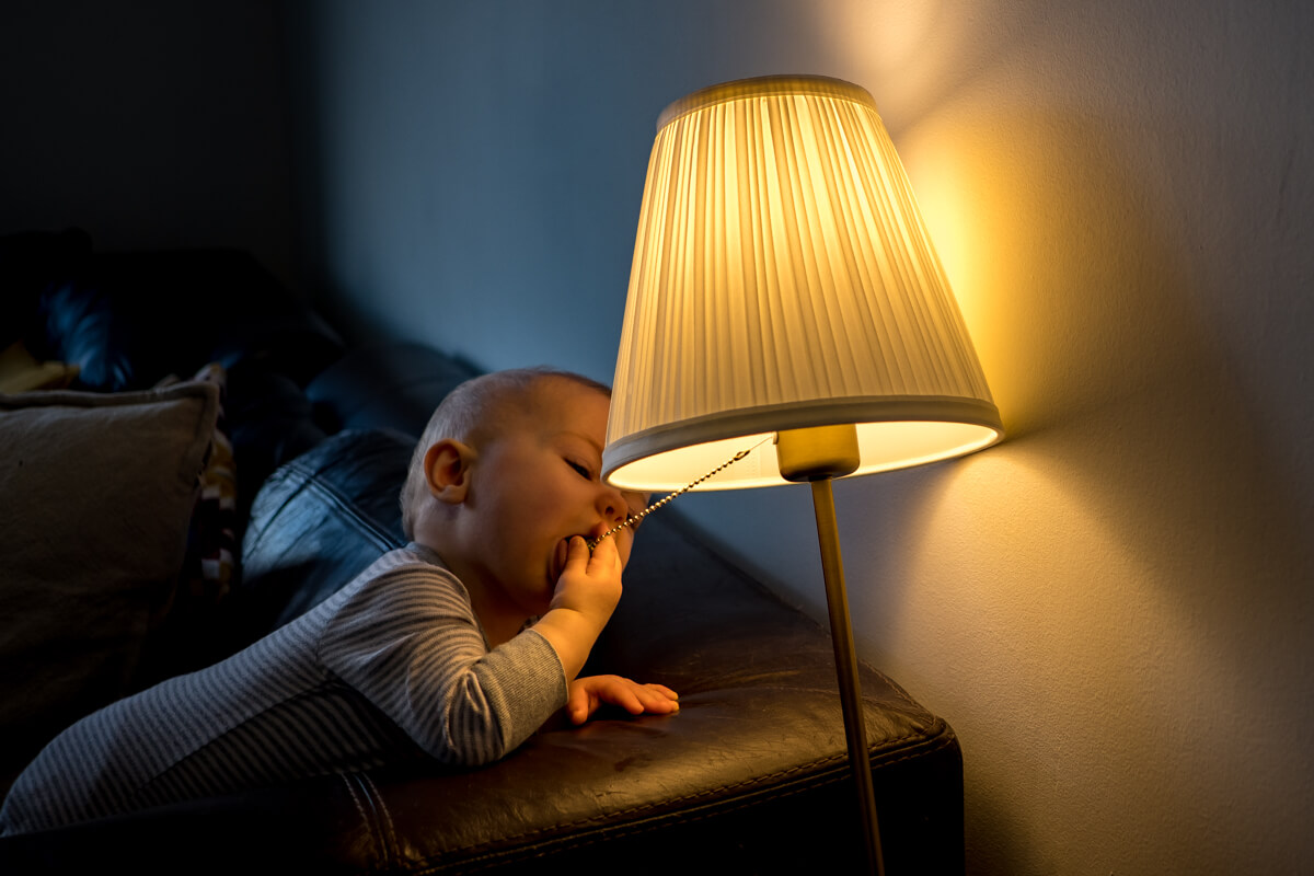 Baby licking a lamp.